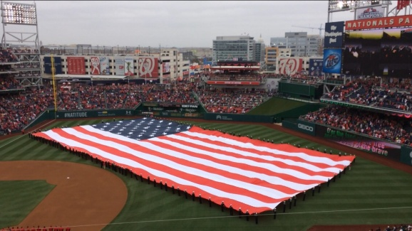 The American Flag is held in the outfield as the National Anthem is sung